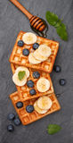 Traditional Belgian waffles with blueberries, banana and honey Stock Image