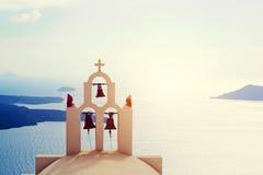 Traditional bells and cross over Aegean sea. Santorini Greece. Oia town on Santorini island, Greece. Traditional bells and cross over the Caldera, Aegean sea royalty free stock image