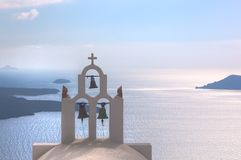 Traditional bells and cross over Aegean sea. Santorini Greece Royalty Free Stock Images