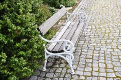 The traditional bench alocated on cobblestone sidewalk Royalty Free Stock Images