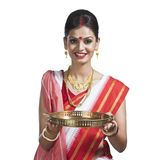 Traditional Bengali woman holding pooja thali. And smiling Royalty Free Stock Photo