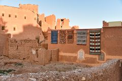 Traditional berber house in Morocco at sunrise. Traditional Moroccan mudbrick house with handmade carpets on a wall in a village at sunrise, Atlas Mountains Royalty Free Stock Photography