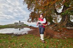 Traditional Bergamo bagpiper of Italian Alps in an autumnal rural context.  royalty free stock images
