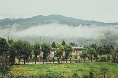 Traditional Bhutanese architectures in a village near Bumthang, Bhutan. South Asia. View of foggy hills Royalty Free Stock Photo