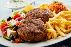 Traditional bifteki with Greek salad and chips. Traditional bifteki, minced beef meat balls, with fresh Greek salad, domatrizo and fried potato chips stock images