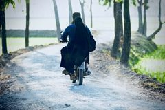 Traditional bikers are biking in a village road photograph stock images