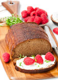 Traditional black rye bread with raspberries and thyme and soft Royalty Free Stock Images