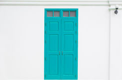 Traditional blue door wooden of an old on white wall. In Thailand Royalty Free Stock Images