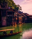 A traditional boat and buildings on waterfront in Fenghuang, Hun Royalty Free Stock Photos