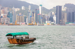 Traditional Boat in front of Hong Kong Harbour Skyline Stock Photography
