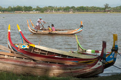 Traditional boat on the lake near U-bein Bridge in Myanmar. Stock Photos