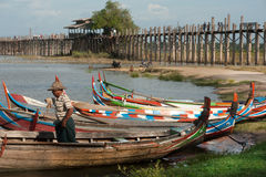 Traditional boat on the shore of the lake near U-bein Bridge. Royalty Free Stock Image