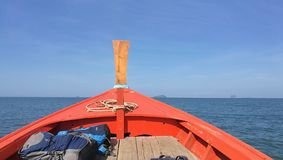 Traditional boat at South of Thailand heading to the sea with sharp horizon, blue ocean and blue sky stock photography