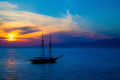 Traditional boat at sunset in Santorini island Stock Photo