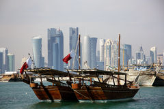 Traditional boats and the Doha skyline. Traditional Qatari boats and the Skyline of a financial and business district of Doha, the capital city of Qatar. View Royalty Free Stock Photography