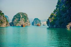 Traditional boats floating among the rock islands of Halong Bay royalty free stock photos