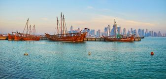 Traditional boats in Qatar. The rippled waters of Persian Gulf with scenic dhow boats in harbor of Doha with numerous modern skyscrapers on the background, Qatar royalty free stock photo