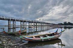 Traditional boats at U Bein bridge. Amarapura. Mandalay region. Myanmar. U Bein Bridge is a crossing that spans the Taungthaman Lake near Amarapura in Myanmar Stock Image