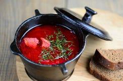 Traditional borsch of Ukrainian origin from beets, carrots, cabbage, potatoes, onions in a cast-iron pot . Original serving Stock Photos