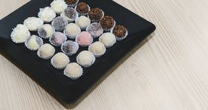 Traditional brazilian sweets - brigadeiros - over wood background. stock photo