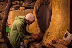 Traditional bread baking in a kiln. A traditional bread baker checking the dough in the kiln stock photo
