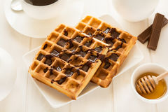 Traditional breakfast: coffee, belgian waffles with honey and chocolate sauce Stock Photo