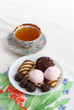 Traditional breakfast concept with colorful cup of tea, sweets and biscuits on white tablecloth with colorful print Stock Image