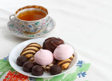 Traditional breakfast concept with colorful cup of tea, sweets and biscuits on white tablecloth with colorful print Royalty Free Stock Photo