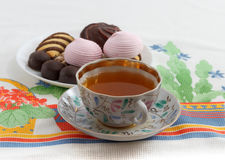 Traditional breakfast concept with colorful cup of tea, sweets and biscuits on white tablecloth with colorful print Royalty Free Stock Photography