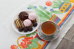 Traditional breakfast concept with colorful cup of tea, sweets and biscuits on white tablecloth with colorful print Stock Images