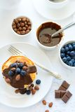 Traditional breakfast concept. Stack of pancakes with chocolate sauce, blueberries and nuts. On white table cloth. Selective focus Royalty Free Stock Images