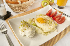Traditional breakfast - fried eggs and cottage cheese. Traditional, wholesome breakfast - fried eggs, cottage cheese, tomatoes, orange juice and kiwi fruit Stock Photography