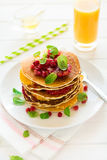 Traditional breakfast: stack of pancakes with orange slices and pomegranate seeds decorated mint leaves stock photography