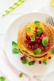 Traditional breakfast: stack of pancakes with orange slices and pomegranate seeds decorated mint leaves Stock Images