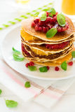 Traditional breakfast: stack of pancakes with orange slices and pomegranate seeds decorated mint leaves Stock Image