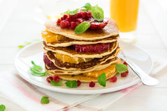 Traditional breakfast: stack of pancakes with orange slices and pomegranate seeds decorated mint leaves Stock Photo