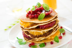Traditional breakfast: stack of pancakes with orange slices and pomegranate seeds decorated mint leaves Stock Photos