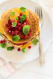 Traditional breakfast: stack of pancakes with orange slices and pomegranate seeds decorated mint leaves Royalty Free Stock Images