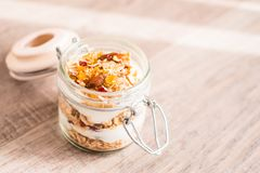 Traditional breakfast from Switzerland. Jar of homemade muesli bircher with plain yogurt, toasted oat flakes, almonds, peanuts, dr. Ied fruits and honey on a stock photography
