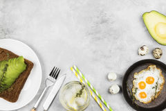 Traditional breakfast - toast from rye bread with avocado, fried eggs from quail eggs, lemonade on a light background. Top view. Copy space. Food background Royalty Free Stock Photo