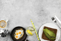 Traditional breakfast - toast from rye bread with avocado, fried eggs from quail eggs, lemonade on a light background. Top view. Traditional breakfast - toast Stock Image