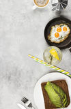 Traditional breakfast - toast from rye bread with avocado, fried. Eggs from quail eggs, lemonade on a light background. Top view, copy space. Food background Stock Photo