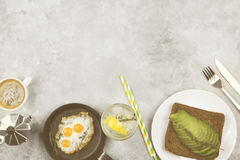 Traditional breakfast - toast from rye bread with avocado, fried. Eggs from quail eggs,  lemonade on a light background. Top view, copy space. Food background Stock Images