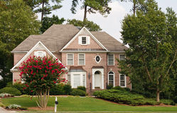 Traditional Brick Home with Blooming Crepe Myrtle Royalty Free Stock Photography
