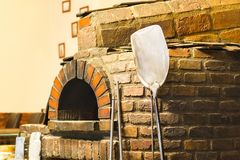 Traditional brick oven. Pizza paddle leaning against stone. Traditional brick oven. Pizza paddle leaning against stone in an old kitchen Stock Images