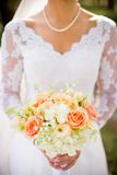 Traditional bride with beautiful orange, pink, and white wedding bouquet of flowers. Traditional bride holding wedding bouquet of flowers consisting of Hydrangea Stock Photos
