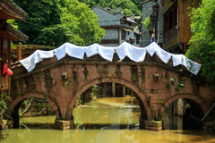 Traditional Bridge Crossing the Canal. Oriental Asian Architecture. Bridge Across the River with Drying Bed Sheets Royalty Free Stock Photography