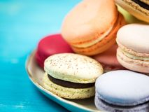 Brightly colored French macarons. Traditional brightly colored French macaroons on a hand-made plate, set on a blue wooden board, close-up view Royalty Free Stock Photography