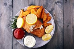 Traditional British fish and chips with potato and lemon. Traditional British fish and chips with potato and lemon stock images