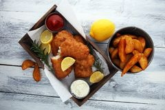 Traditional British fish and chips with potato and lemon. Traditional British fish and chips with potato and lemon stock image